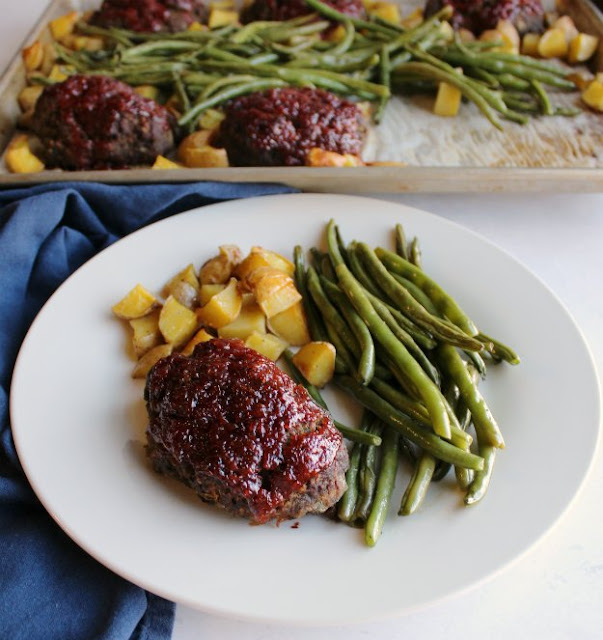 dinner plate loaded with mini meatloaf, green beans and potatoes with pan in background