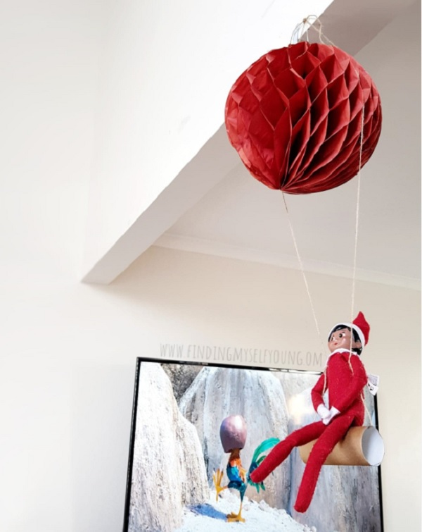 Elf on the shelf swinging on a toilet paper roll swing