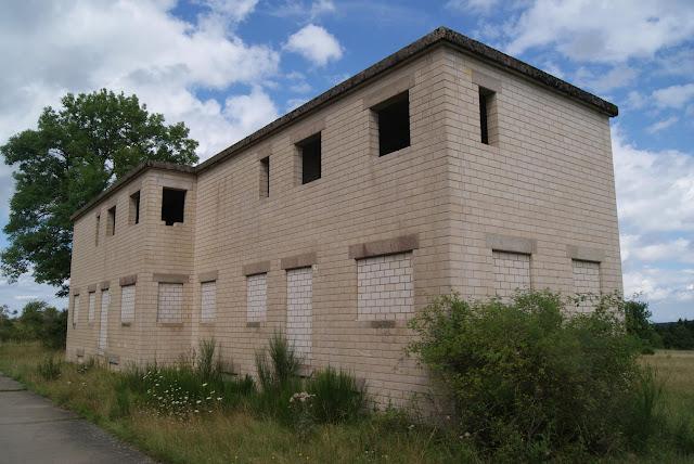 Ein einfaches, rechteckiges Haus mit zugemauerten Fenstern