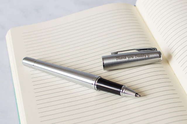 "A silver coloured roller ball pen by Parker at Pen Heaven with etching on the lid saying ""Thank you Daddy G"" on an open lined notepad"