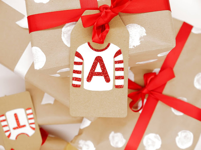 a shot taken from above of presents wrapped in brown kraft paper, tied with white ribbons. Some have white spots and red ribbons. On the top present is a kraft tag with a white glitter christmas jumper stuck on it, with red stripes stuck on the sleeves and a red A on the chest.