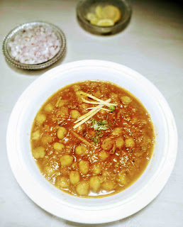 Serving chole(chickpeas curry) with chopped onion and lemon wedges for chole chickpeas recipe