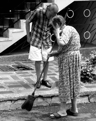Elderly man watching an edlerly woman sweeping.