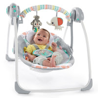 baby in a grey and coloured baby swing