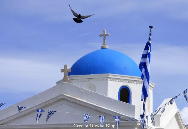 Lecący gołąb nad cerkwią. Biała grecka cerkiew z niebieską kopułą oraz narodową flagą na tle nieba.
