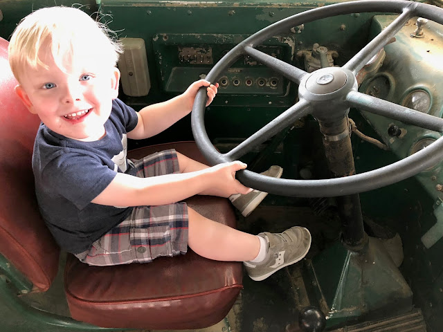 Smiling kid sitting on old bus pretending to turn steering wheel.