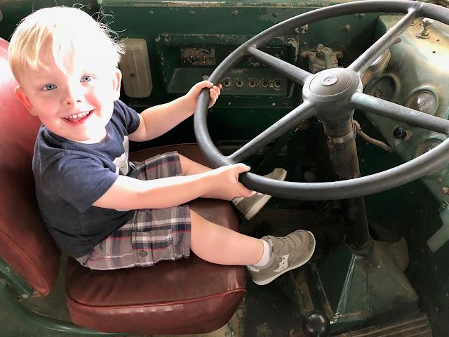 Smiling kid sitting on old bus pretending to turn steering wheel.