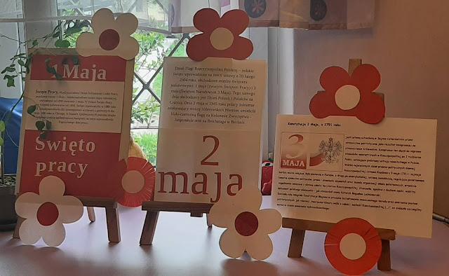 Wystawka na trzech sztalugach. Na pierwszej na biało czerwonym tle napis 1 Maja Święto pracy i krótka historia święta. Na drugie sztaludze na białym tle napis 2 maja i krótka historia święta. Na trzeciej sztaludze godło Polski, napis Konstytucja 3 maja z 1971 roku oraz krótka historia święta.