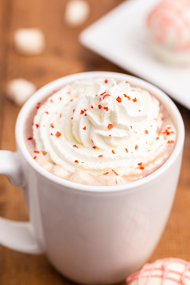 Very close up photo of a white mug full of hot chocolate made with a Keto Valentine Hot Chocolate Bomb and topped with whipped cream and red edible glitter flakes.
