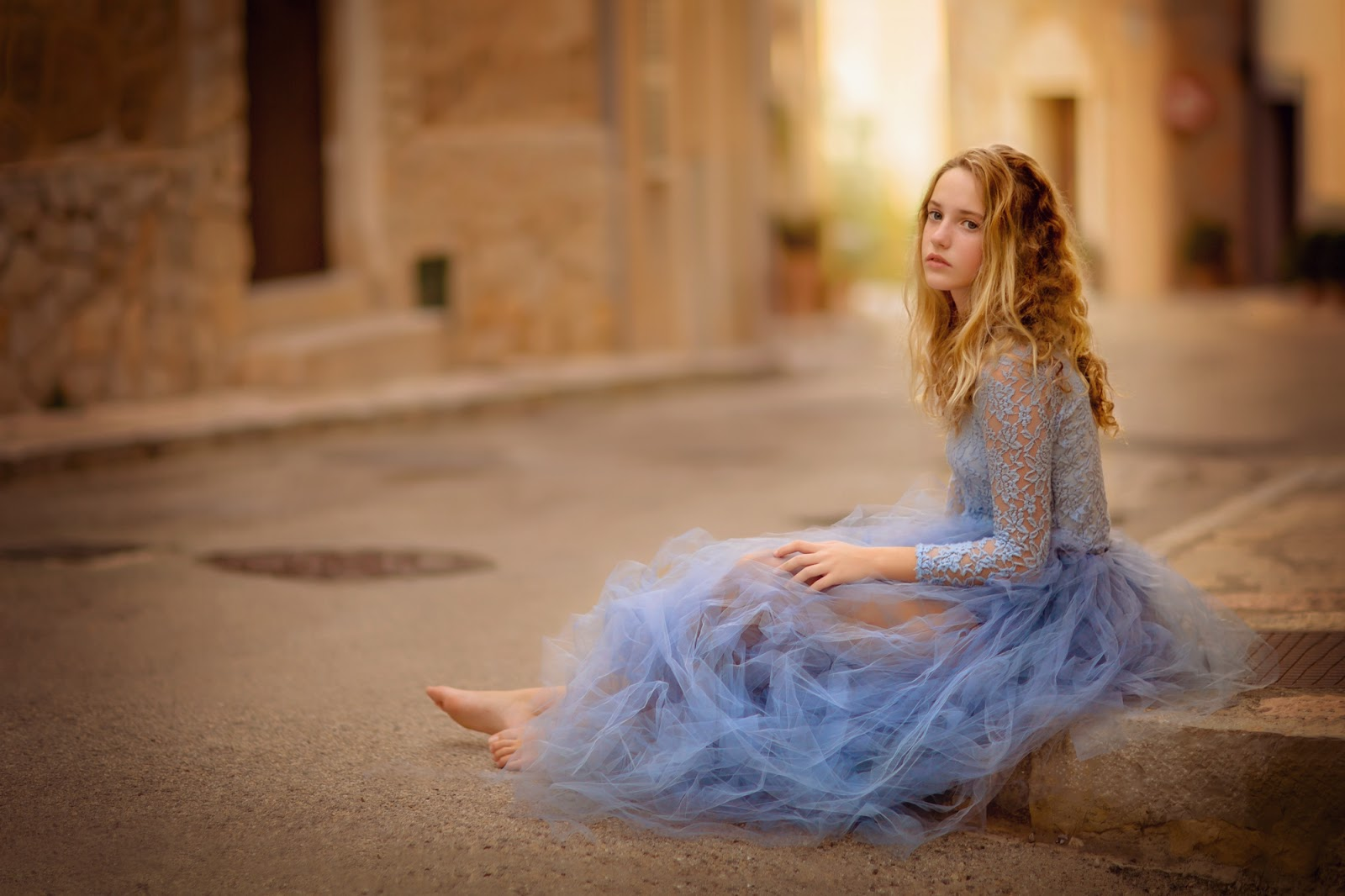 Canon portrait of a young woman sitting on the side walk in a gorgeous blue dress during sunset at Mallorca by Willie Kers