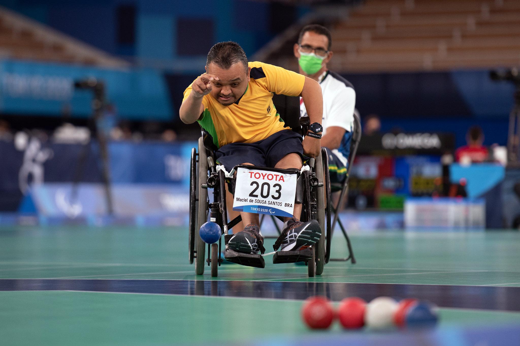 Maciel, sentado em uma cadeira de rodas, arremessa uma bola azul na área de competição