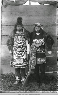 Two people wearing beaded regalia.