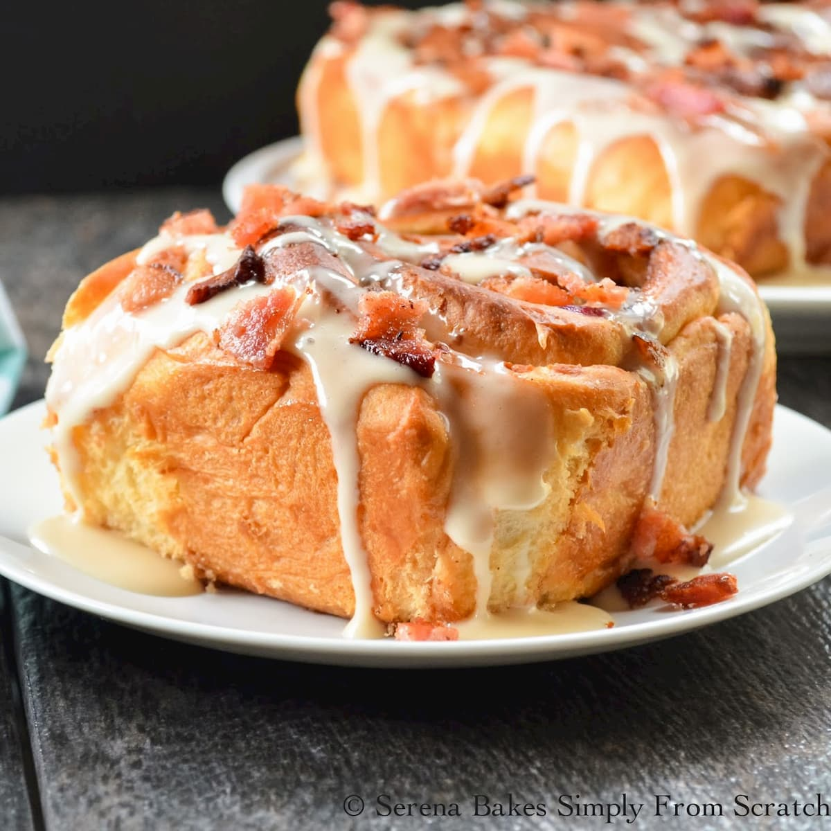 Blueberry Bacon Cinnamon Rolls drizzled with Maple Glaze and topped with bacon on a white plate.