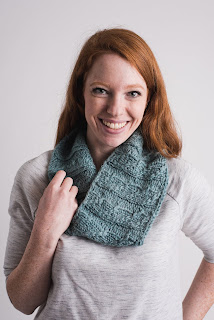 A woman wearing a light blue, worsted-weight, cabled cowl that hangs loosely about her neck.