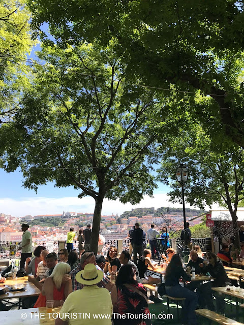People sitting in a beergarden in the shade of trees with a view over red rooftops.
