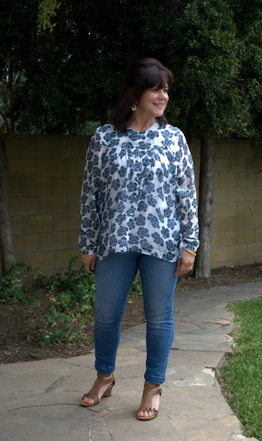 skinny jeans and floral blouse with wedge sandals.