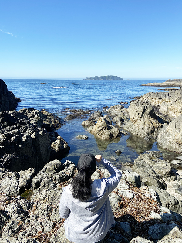 Vancouver beauty, life and style blogger Solo Lisa sits on a rock overlooking the secret cove at Wickaninnish Inn, Tofino.