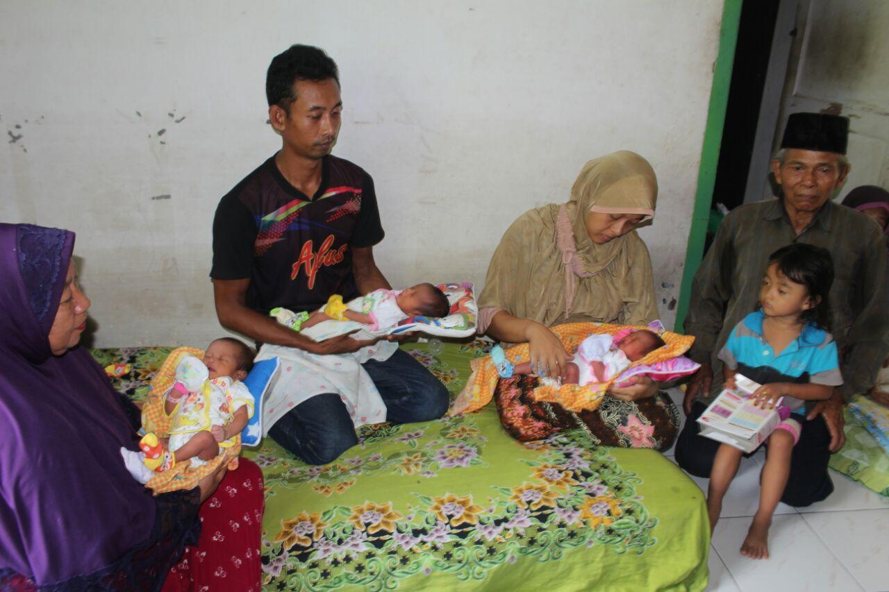 Tiga bayi kembar dari Asahan saat dipangku orangtuanya dan keluarga.