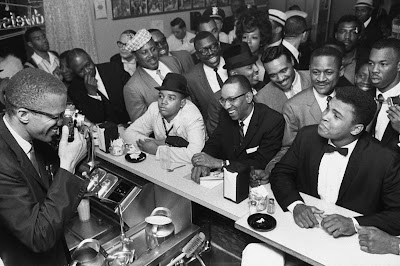 photo of then-Cassius Clay at lunch counter surrounded by fans with Malcolm X taking a picture in Miami, 1964