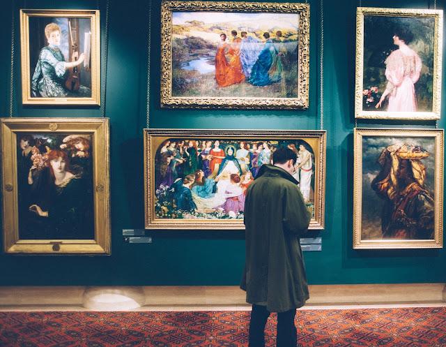 persona de raza blanca mirando una de obra de arte en un museo