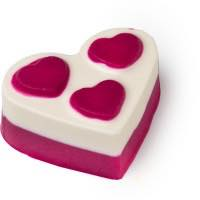 A heart shaped pink and white bath oil with pink hearts on the top of It on a bright background