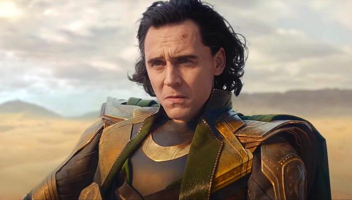 Imagem: o personagem Loki, em sua armadura verde com detalhes dourados e capa preta, sentado em um deserto.