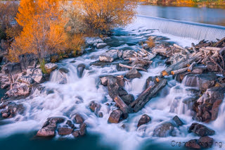 Fine art landscape photograph of the Idaho Falls waterfall with logs, rocks, and autumn leaves by Cramer Imaging