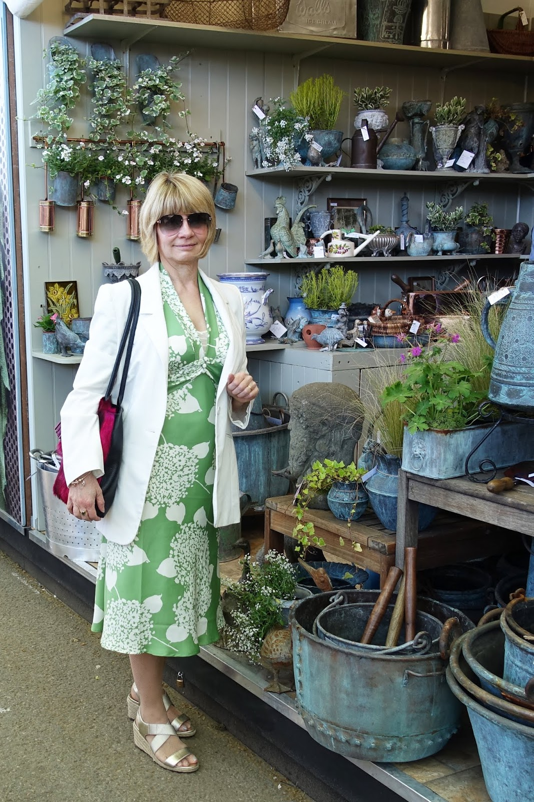 In front of a stall selling copper planters and garden decorations. Is This Mutton's Gail Hanlon in green and cream hydrangeas dress