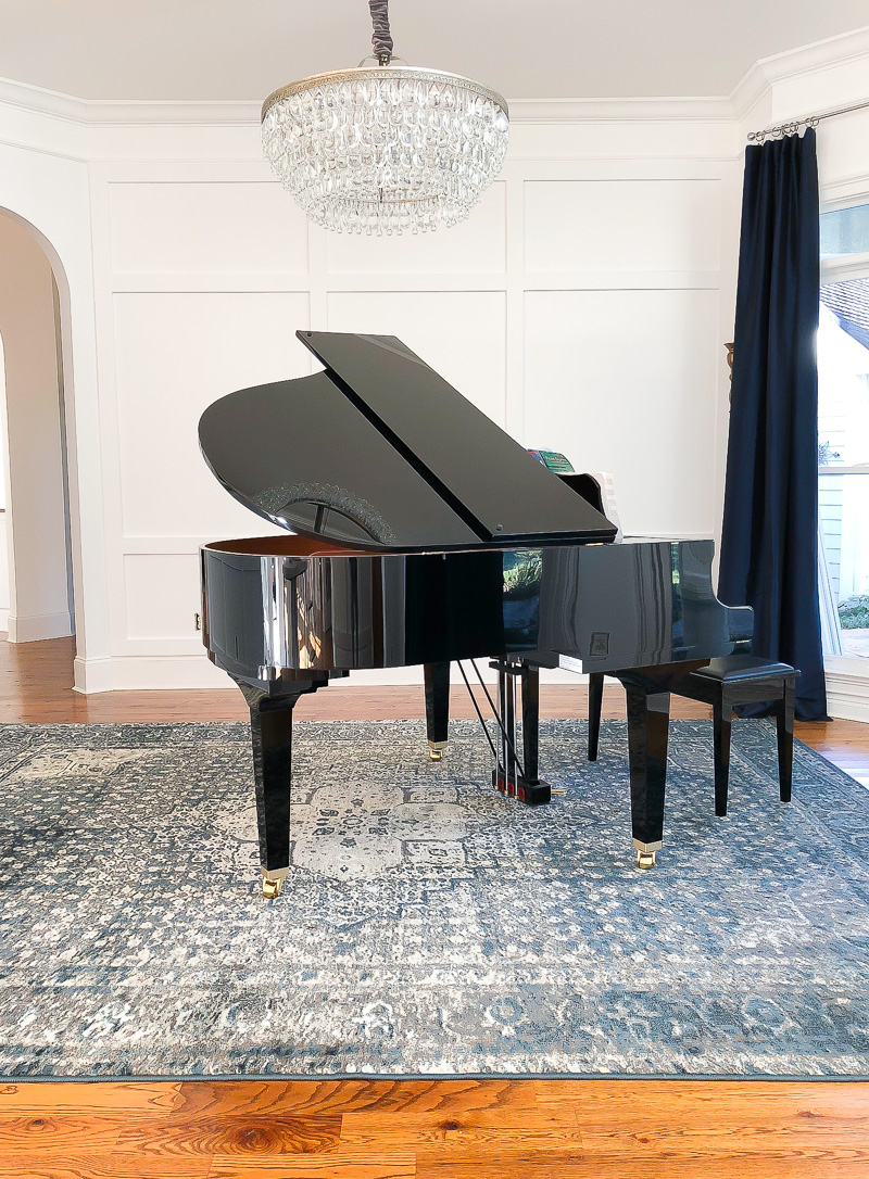 Piano room with chandelier and white walls