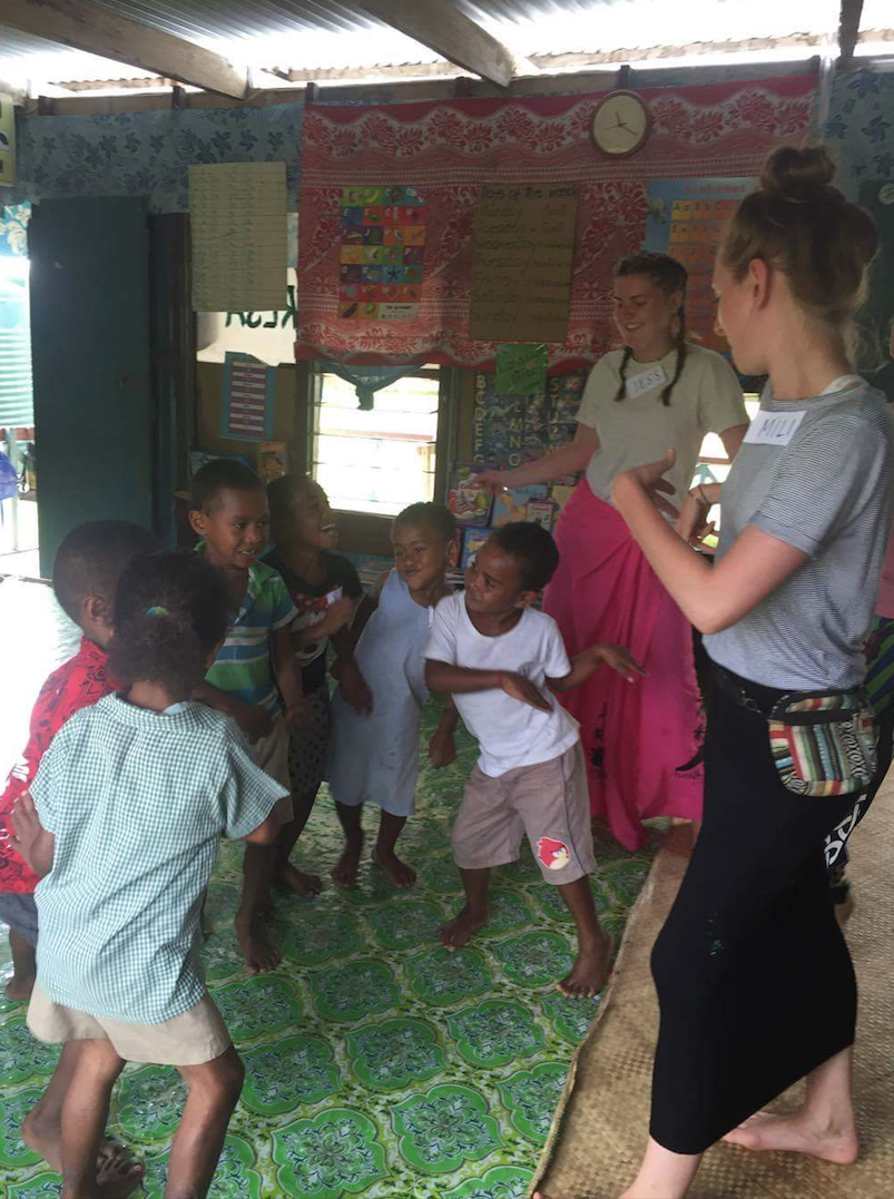 The volunteers and the children dancing in the classroom