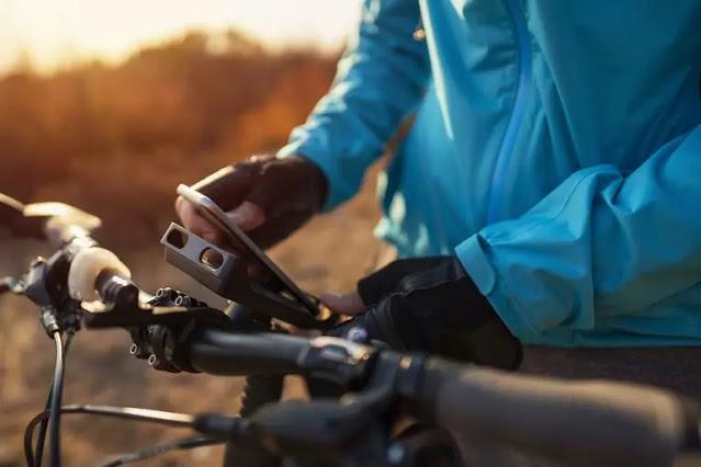 un ciclista de montaña que conecta su teléfono a un soporte para bicicleta