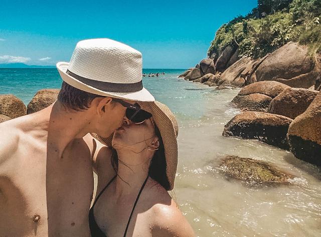 Casal de beijando na frente do mar