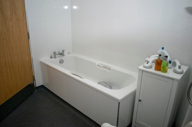 Large bath in wetroom with grab rails