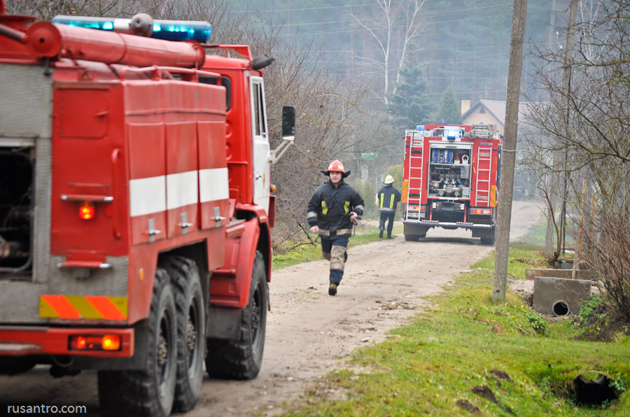 Ugunsdzēsējs skrien no vienas ugunsdzēsēju mašīnas pie otras