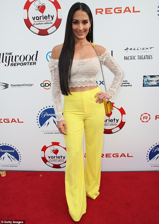Nikki Bella flaunts her cleavage and midriff in cropped lace top and yellow pants