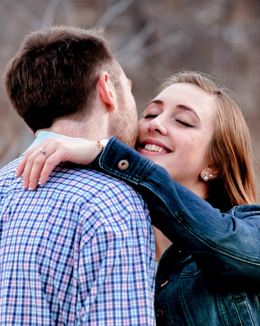 a couple embraces for a photo during their engagement session in Boulder Colorado