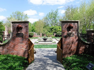 an open gate in an ornate brick wall reveals a victorian garden at Lauritzen Gardens in Omaha