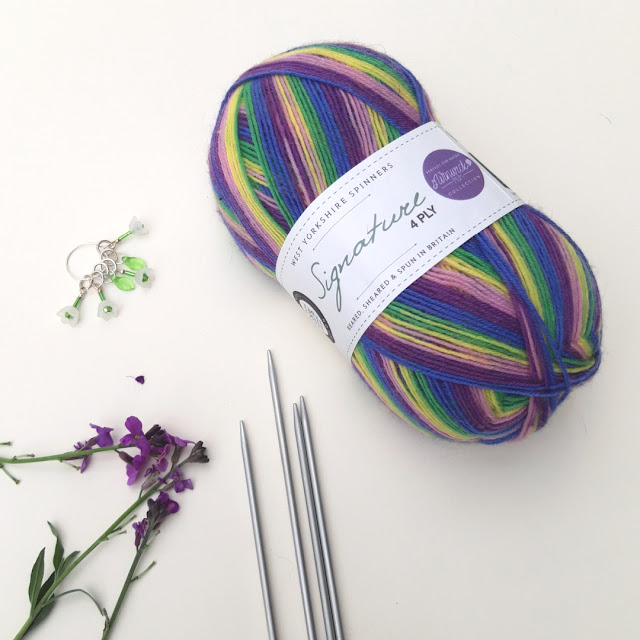 A ball of multi-coloured Winwick Mum Wildflower yarn on a cream background with purple flowers, knitting needles and some green flower-shaped stitch markers