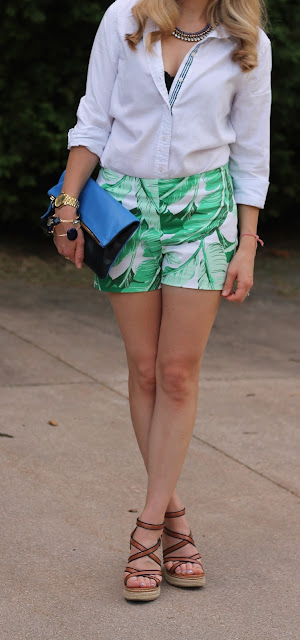 white button up, palm print shorts, wedges, blue clare v. clutch