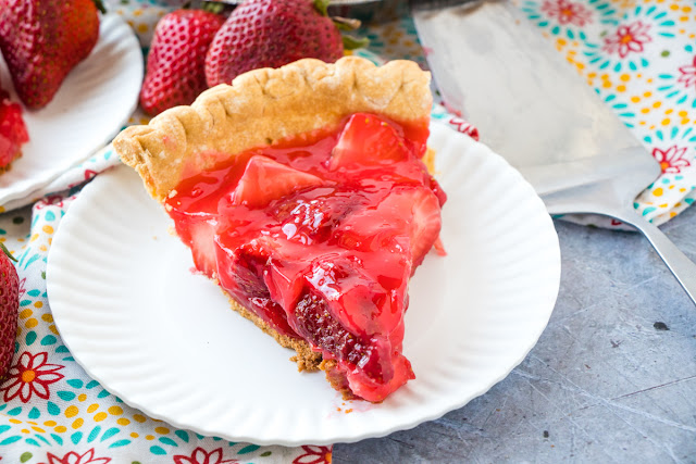 Slice of fresh strawberry pie made with gelatin surrounded by strawberries on a white plate and colorful napkin