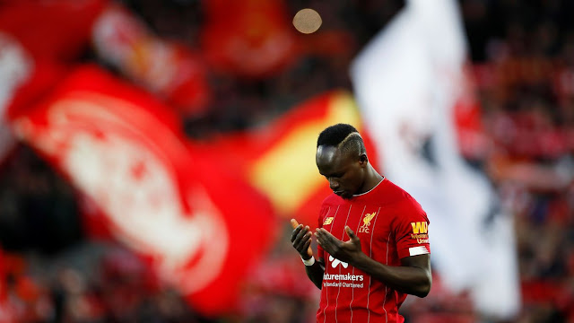 Sadio Mane prepares for kick-off, with a sea of Liverpool flags behind him at Anfield before a premier league match against Tottenham