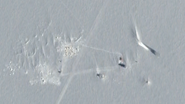 This image shows lots of different tracks in the snow near the UFO.