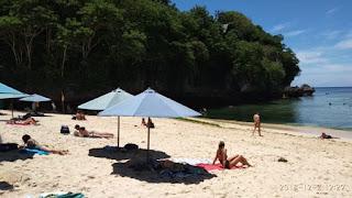 Berjemur dengan payung di Pantai Pandawa Bali