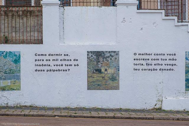 Muro com reproduções de pinturas de Miguel Bakun e textos de Dalton Trevisan