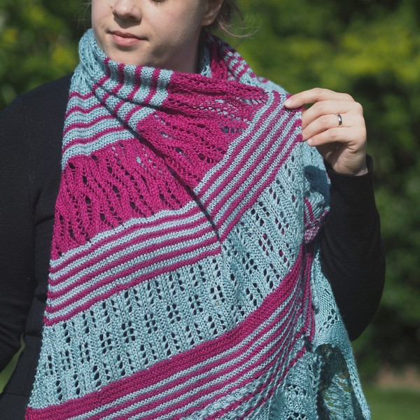 woman wearing seafoam and magenta lace wrap around neck and holding out part of the wrap