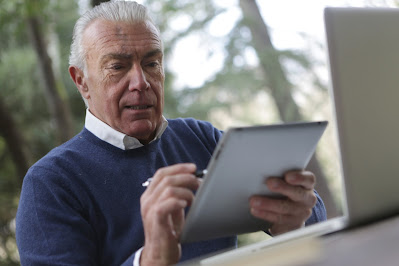 an older man uses an iPad
