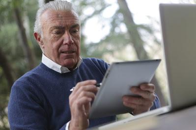 an older man uses an iPad