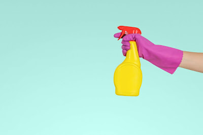 hand with purple cleaning glove holding and ready to squirt  a spray bottle