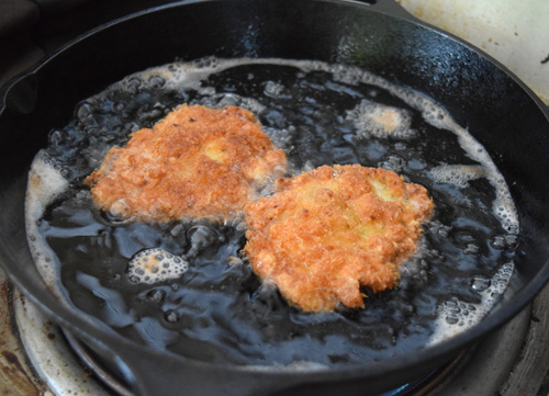 Fried pork cutlets frying in a cast iron skillet