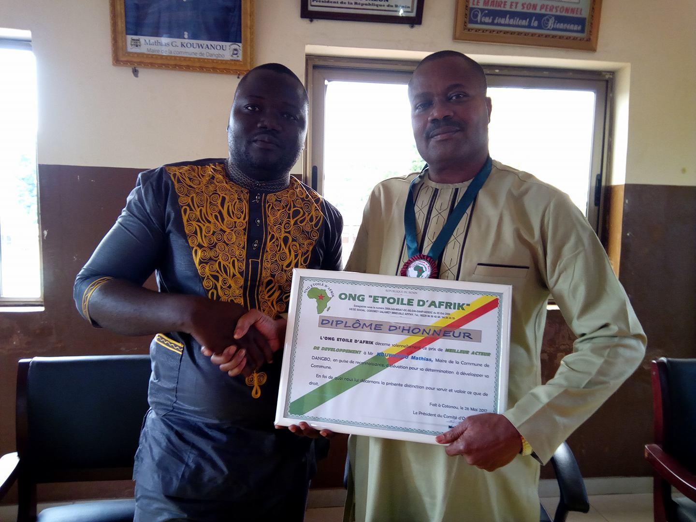 Mathias G. Kouwanou recevant sa distinction des mains de Mohamed Badélé,  Pdt de l'Ong Etoile d'Afrik